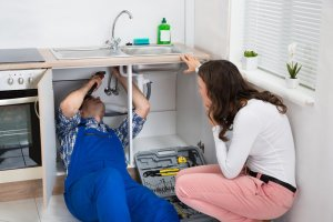 A licensed plumber performing a drain cleaning