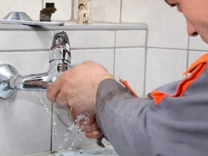Picture of a plumber fixing a leaky faucet