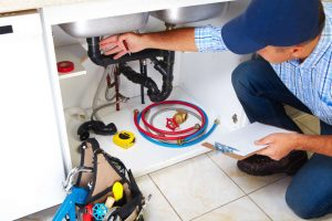 Picture of a plumber checking an unclogged drain