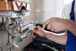 Picture of a plumber repairing boiler