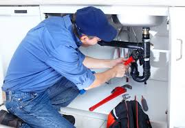 Photo of a plumber fixing sink drainage