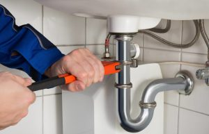 Photo of a plumber tightening drainage pipe