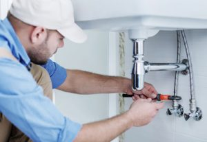 Picture of a plumber fixing sink drainage