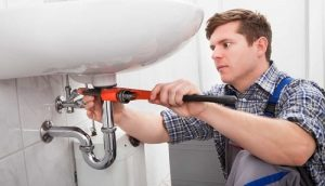 photo of a professional plumber tightening pipe