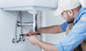 Picture of a plumber fixing sink drain