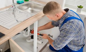 picture if a plumber repairing sin drainage