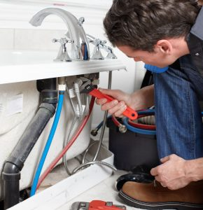 plumber professionally repairing bath tub picture