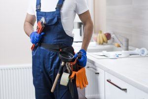 picture of a professional plumber with plumbing tools
