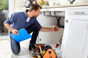 plumber checks leaks of a sink drain photo