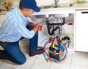 plumber photo fixing broken sink drain