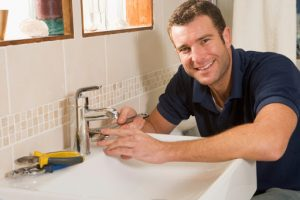 professional plumber poses in front of a sink faucet photo
