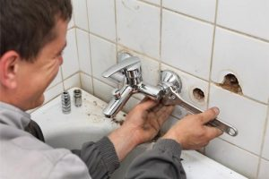 plumber removing old faucet photo