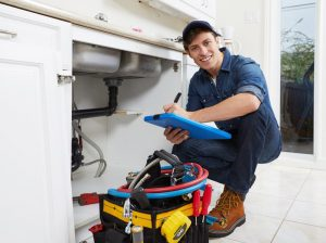 plumber smiles on a camera while working photo