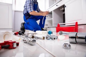 professional plumber with wrench and tools photo