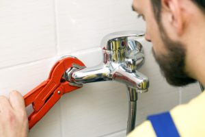 licensed plumber installing faucet photo
