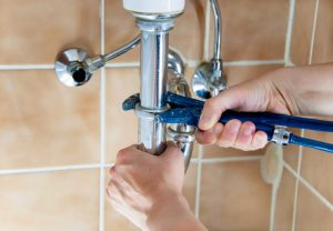 photo of a plumber fixing sink drain photo