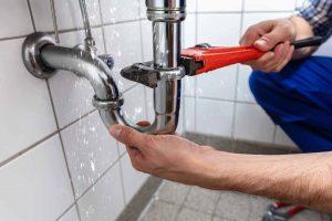 plumber fixing sink pipe photo