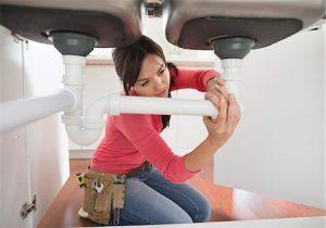 female plumber repairing sink drain photo