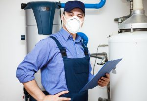 plumber technician servicing hot water heater photo