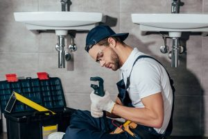 plumber with a wrench photo while installing bathroom sink