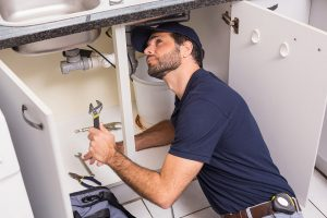 professional plumber checking kitchen sink for leaks