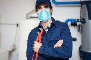 smiling plumber repairing hot water heater photo