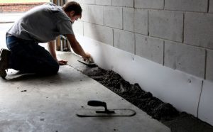 Picture of a man waterproofing a basement