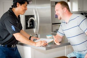 plumber and client shake hands after repair photo