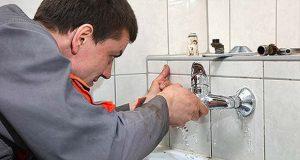 plumber fixing faucet photo